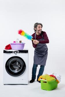 Vooraanzicht gelukkige huishoudster man met stofdoek staande in de buurt van wasmachine op witte achtergrond