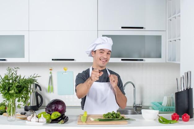 Vooraanzicht gelukkige jonge chef-kok in uniform wijzend op camera