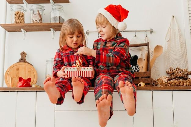 Vooraanzicht gelukkige jonge geitjes die gift van kerstmis houden