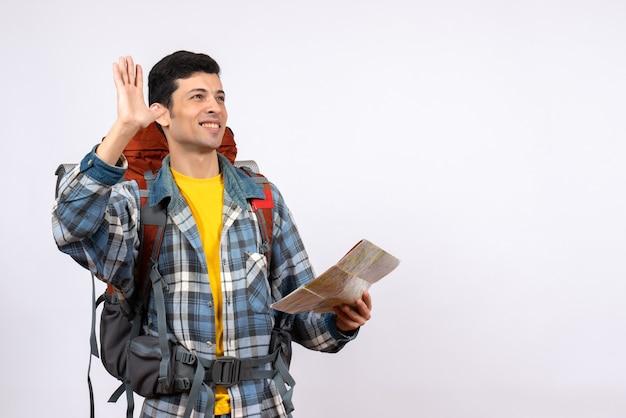 Vooraanzicht gelukkige jonge kampeerder met kaart die van de rugzakholding iemand begroet