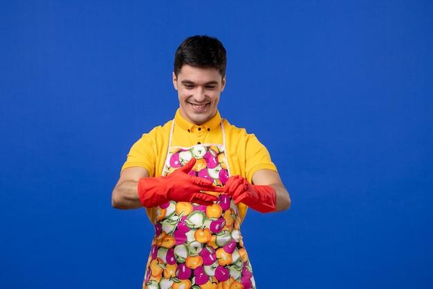 Vooraanzicht gelukkige jonge man die zijn handschoenen uittrekt op blauwe ruimte