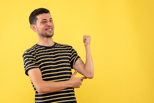 Vooraanzicht gelukkige jonge man in zwart-wit gestreepte t-shirt gele geïsoleerde achtergrond