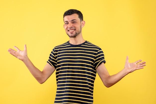Vooraanzicht gelukkige jonge man in zwart-wit gestreepte t-shirt opening handen op gele geïsoleerde achtergrond
