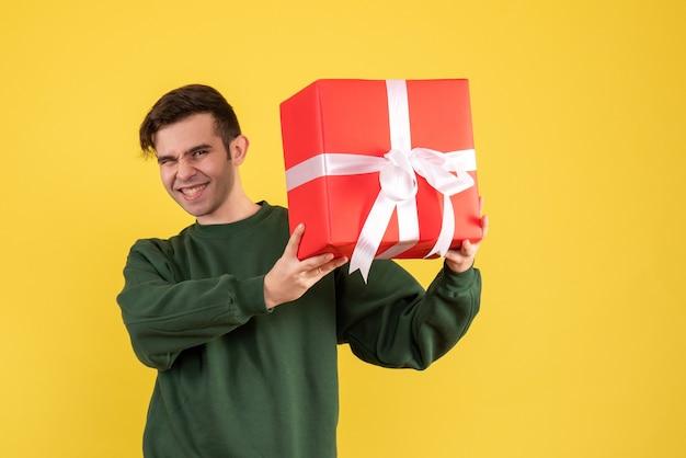 Vooraanzicht gelukkige jonge man met groene trui staande op geel