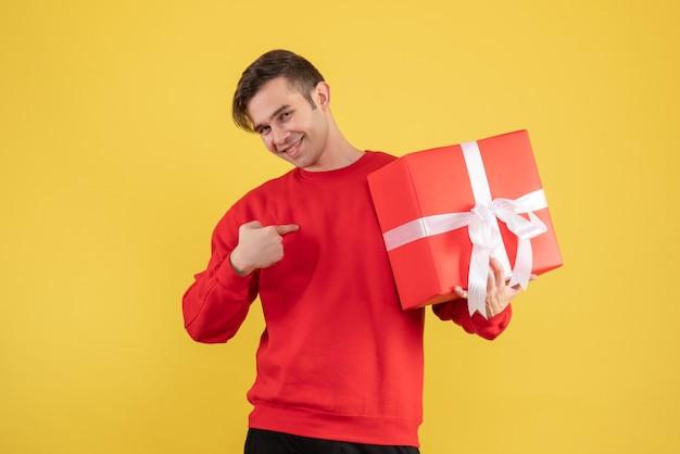 Vooraanzicht gelukkige jonge man met rode trui staande op geel