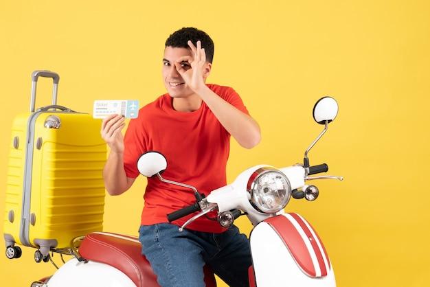 Vooraanzicht gelukkige jonge man op bromfiets bedrijf kaartje okey teken voor zijn bord zetten