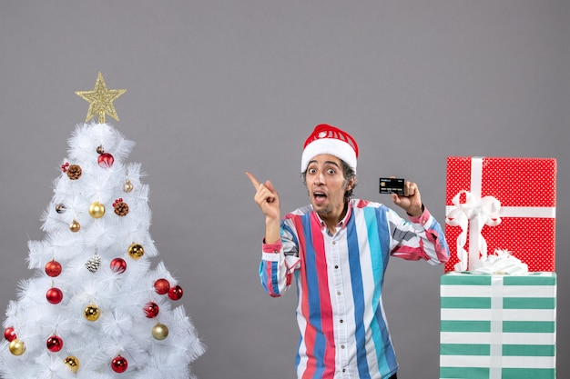 Vooraanzicht gelukkige jonge man wijsvinger met witte kerstboom