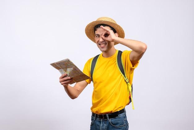 Vooraanzicht gelukkige jonge toerist die met de kaart van de rugzakholding handverrekijker maakt