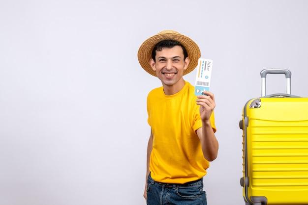 Vooraanzicht gelukkige jonge toerist die zich dichtbij gele koffer bevindt die vliegticket steunt