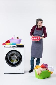 Vooraanzicht gelukkige kerel met geknipperd oog dat verkoopteken omhoog houdt dat dichtbij wasmachine op witte achtergrond staat