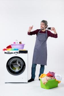 Vooraanzicht gelukkige man die kaart omhoog houdt die dichtbij wasmachine op witte achtergrond staat