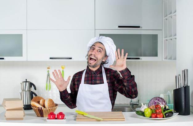 Vooraanzicht gelukkige mannelijke chef-kok die handen opent in de keuken