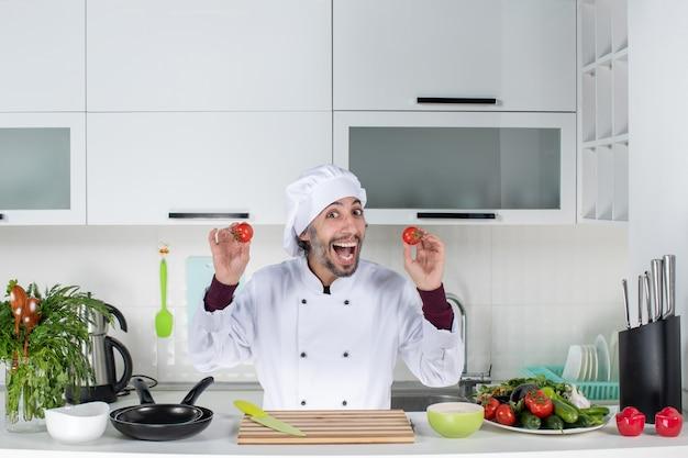 Vooraanzicht gelukkige mannelijke chef-kok in uniform met tomaten in de keuken