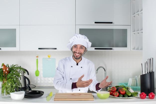 Vooraanzicht gelukkige mannelijke chef-kok in uniform staande achter de keukentafel