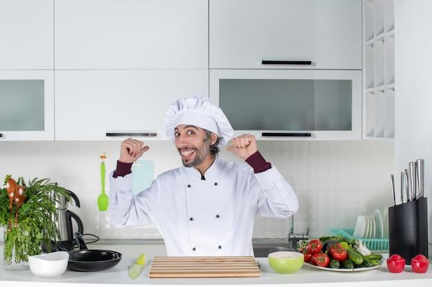 Vooraanzicht gelukkige mannelijke chef-kok in uniform wijzend naar achter in de keuken