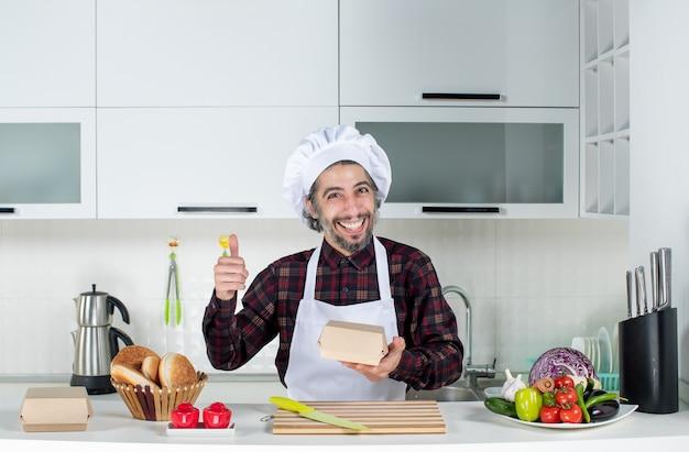 Vooraanzicht gelukkige mannelijke chef-kok met doos die duim opgeeft in de keuken