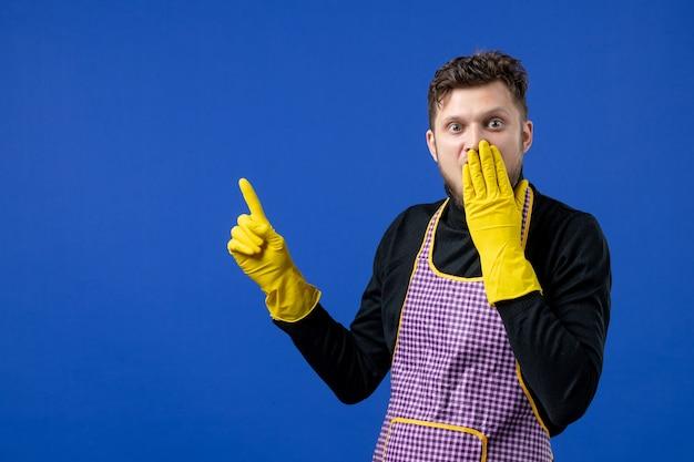Vooraanzicht gelukkige mannelijke huishoudster in zwarte trui die hand op zijn gezicht legt op blauwe geïsoleerde ruimte
