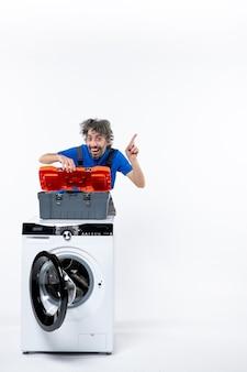 Vooraanzicht gelukkige reparateur die gereedschapstas opent achter witte wasmachine op witte ruimte