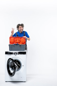Vooraanzicht gelukkige reparateur die overwinningsteken achter wasmachine op witte ruimte maakt