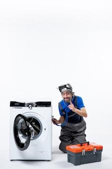 Vooraanzicht gelukkige reparateur die stethoscoop op wasmachine zet die dichtbij wasmachine op witte ruimte zit
