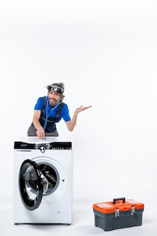 Vooraanzicht gelukkige reparateur met koplamp die stethoscoop op wasmachine op witte ruimte zet