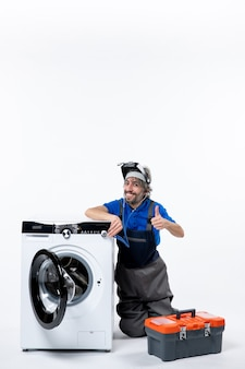 Vooraanzicht gelukkige reparateur zit in de buurt van wasmachine en maakt duim omhoog teken op witruimte