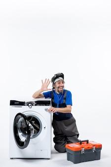 Vooraanzicht gelukkige reparateur zit in de buurt van wasmachine en roept iemand op witte ruimte aan