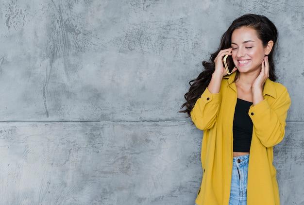 Vooraanzicht gelukkige vrouw die op de telefoon spreekt