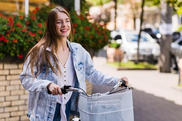 Vooraanzicht gelukkige vrouw met fiets
