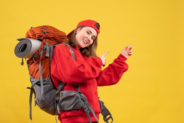 Vooraanzicht gelukkige vrouwelijke reiziger met rugzak wijzende vingers erachter