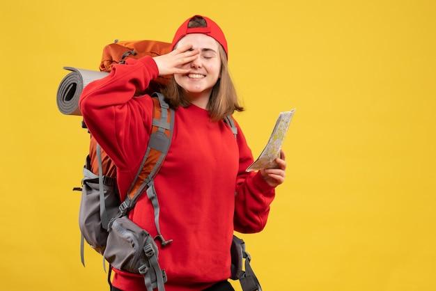 Vooraanzicht gelukkige vrouwelijke wandelaar met rode rugzak met kaart hand op haar oog zetten