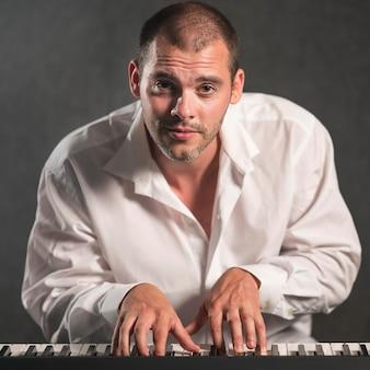 Vooraanzicht gepassioneerde man die toetsenborden speelt