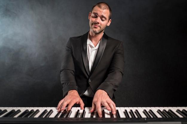 Vooraanzicht gepassioneerde muzikant akkoorden spelen op piano