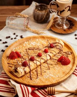 Vooraanzicht gerolde pannenkoek met chocolade glazuur en aardbeien