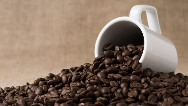 Vooraanzicht geroosterde koffiebonen gemorst uit witte mok