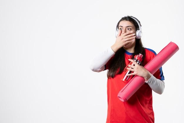 Vooraanzicht geschokt jong wijfje in sportkleren met oortelefoons