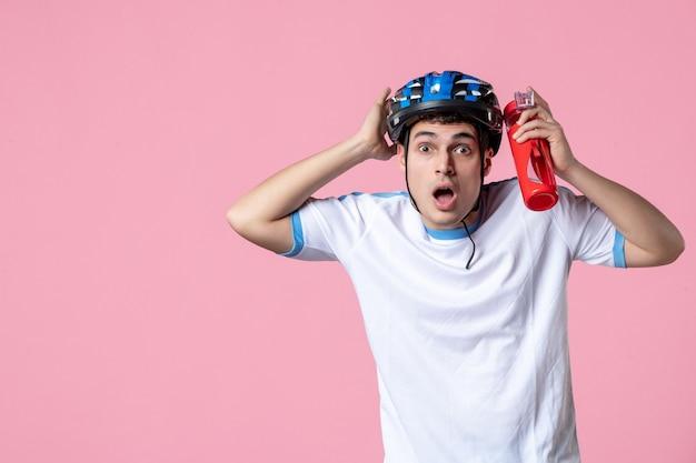 Vooraanzicht geschokt jonge atleet in sport kleding helm en fles water te houden