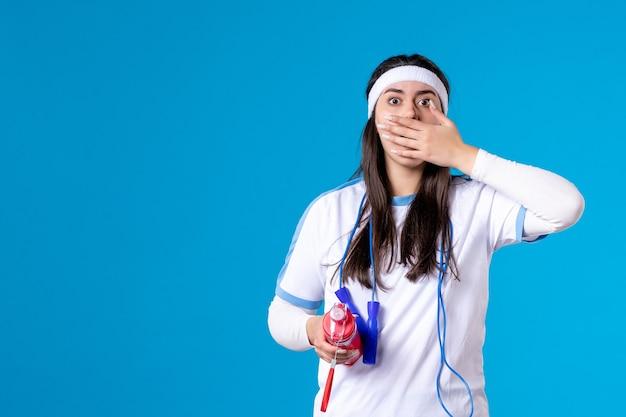 Vooraanzicht geschokt vrij wijfje in sportkleren met fles water op blauw