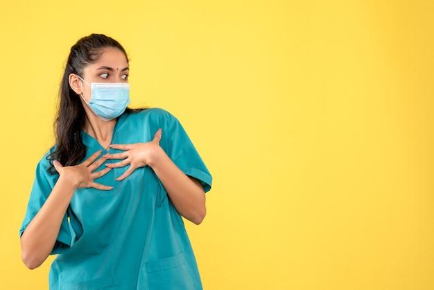 Vooraanzicht geschokt vrouwelijke arts handen op haar borst op gele achtergrond