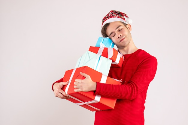 Vooraanzicht gesloten oog jonge man met kerstmuts zijn geschenken stevig vast te houden op witte achtergrond kopie ruimte