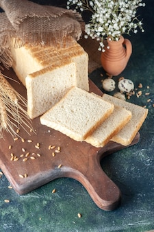 Vooraanzicht gesneden brood op de donkerblauwe achtergrond broodje deeg bakkerij thee ochtend brood gebak eten ontbijt
