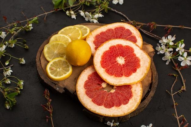 Vooraanzicht gesneden fruit citrusvruchten zoals citroenen en grapefruits op het bureau en grijs