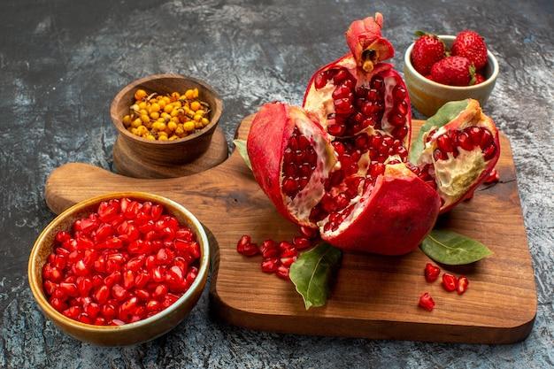 Vooraanzicht gesneden granaatappels met ander fruit op licht bureau kleur vers fruit