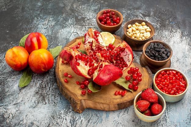Vooraanzicht gesneden granaatappels met ander fruit op licht-donker tafelboomfruit