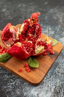 Vooraanzicht gesneden granaatappels vers rood fruit op de lichte tafel fruit rood vers