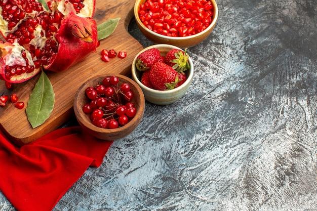 Vooraanzicht gesneden granaatappels vers rood fruit op een licht-donkere tafel