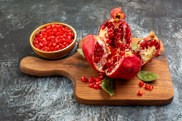Vooraanzicht gesneden granaatappels vers rood fruit op lichte tafel rode verse bessen fruit