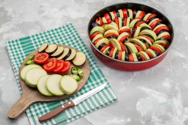 Vooraanzicht gesneden groenten zoals tomaten en aubergines vers en gekookt op wit