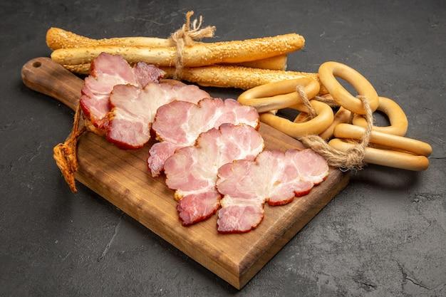 Vooraanzicht gesneden ham met zoete crackers en broodjes op grijze foto vlees eten rauwe varkenskleur