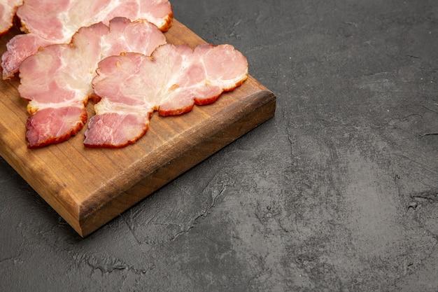 Vooraanzicht gesneden ham op houten bureau en de grijze foto kleur vlees eten maaltijd rauw varken